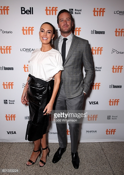 "ARMIE HAMMER wore a grey Prince Of Wales wool jacket with matching grey pants, while his wife ELIZABETH CHAMBERS wore a black leather skirt with white cotton blouse to the premiere of film ""The Birth Of A Nation""."
